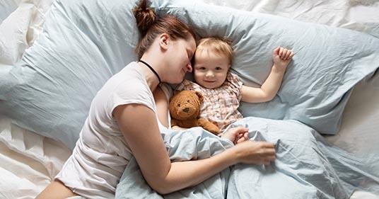 Mère avec hygene de sommeil en pijamas qui dorent avec son enfant.