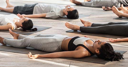 savasana pose diverse yoga class doing yoga nidra