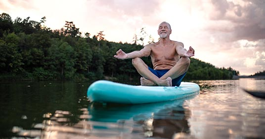 elderly man performing yoga reaping the benefits of yoga for men
