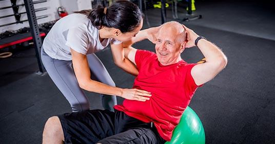Un homme âgé avec un entraîneur faisant de la réadaptation en utilisant des exercices Pilates