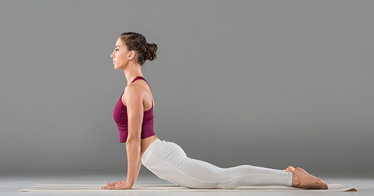 young woman practicing kundalini yoga cobra pose
