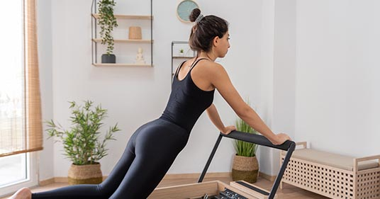 woman doing workout on pilates reformer bed