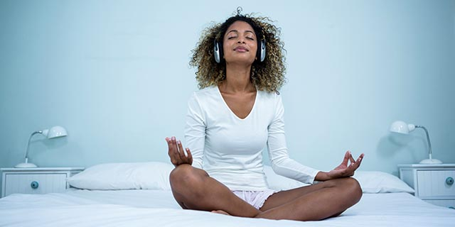 woman listening to music meditation while meditating relaxed
