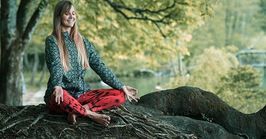 woman doing mindful meditation outdoors to help her cope with stress and pressure