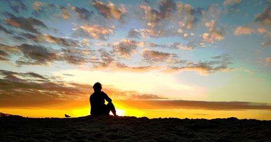 woman practicing morning meditating during sunrise