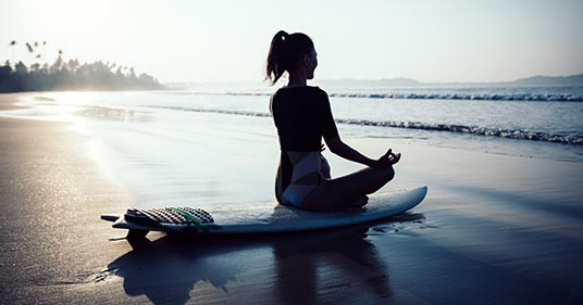 girl sitting in meditation pose on surf board practicing how to clear your mind