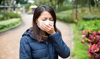 woman wearing a facemask suffering from breathing problems, such as dyspnea