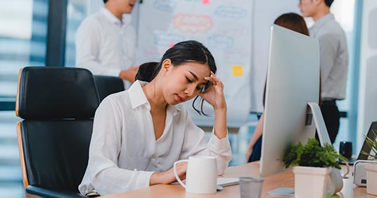 young businesswoman feeling stressed at work in need of workplace stress relief
