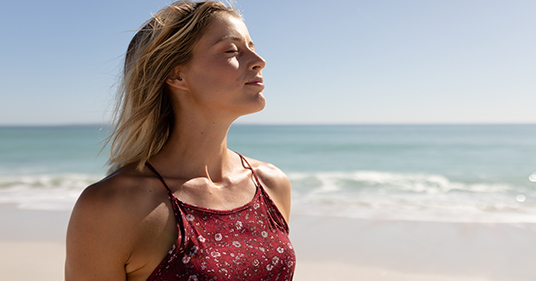young caucasian woman breathing while walking on the beach, not worried about  paradoxical breathing