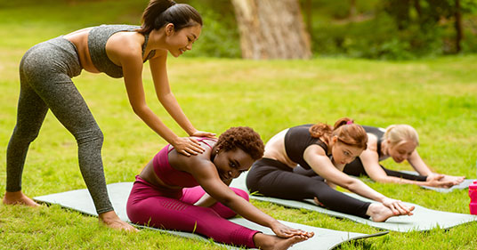 young female yoga instructor teaching gentle yoga to a group outdoors