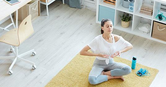 Mujer joven disfrutando de ejercicios de respiración de meditación en casa haciendo 4 7 8 respiración