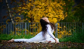 young woman in yoga position trying to achieve kundalini awakening